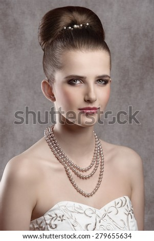 beautiful elegant lady  posing in close-up  shoot with fine hairstyle, cute white dress and precious pearls necklace. Looking in camera  - stock photo