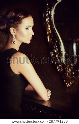 Beautiful elegant lady stands by the mirror in vintage interior. Fashion shot. - stock photo
