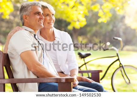 beautiful elegant mid age couple daydreaming retirement outdoors - stock photo