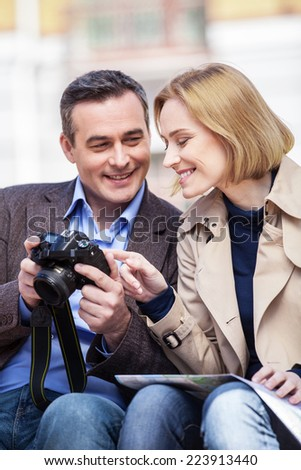 beautiful elegant mid age couple resting outdoors. man holding camera and showing pictures to blond woman
