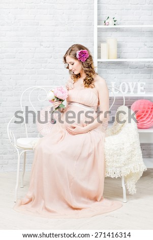 Beautiful elegant pregnant woman with romantic dress, hairstyle and make-up. Studio interior shot.  - stock photo