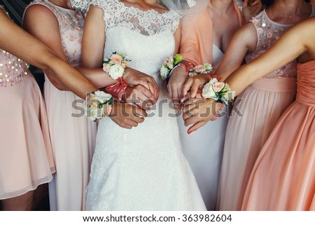 Beautiful elegant slim bridesmaids in delicate pink beige summer dress with bracelets of the luxury fresh roses on the wedding ceremony - stock photo