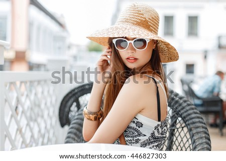 Beautiful elegant stylish woman in vintage hat and sunglasses sitting in a cafe on a sunny day.