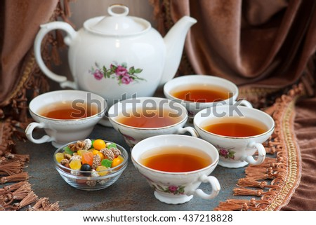Beautiful elegant tea set and fruit mixture on the background of velvet curtains. The dishes are cooked to tea drinking. Pieces of fruit can be eaten with tea. - stock photo