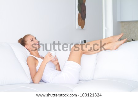 Beautiful elegant woman barefoot in a white dress reclining on a sofa drinking coffee