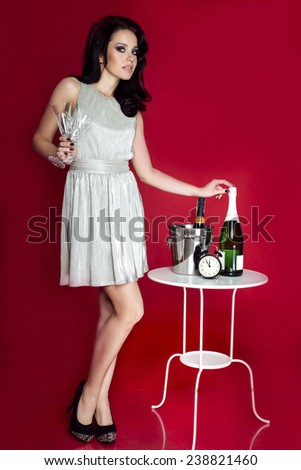 Beautiful elegant woman celebrating, holding champagne and glasses. Girl wearing fashionable silver dress, looking at camera. Red background. - stock photo
