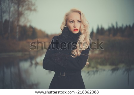 Beautiful elegant woman in a black coat on the river bank - stock photo