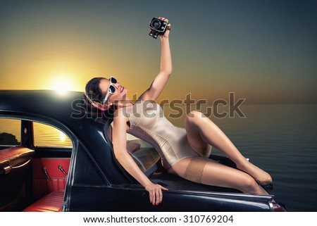 Beautiful elegant woman in pin up style on car with retro camera - stock photo