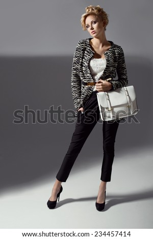 Beautiful elegant woman in stylish cardigan, high heels holding handbag. Fashion shot