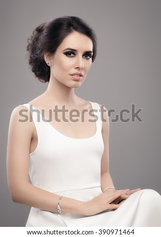Beautiful Elegant Woman in White Dress Wearing Jewelry - Portrait of a gorgeous bride with diamond jewellery accessories  - stock photo