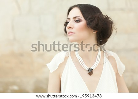 Beautiful elegant woman in white long dress, holding her head up, with a very dignified and strong attitude. - stock photo