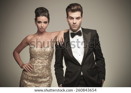 Beautiful elegant woman leaning on her lover while both look at the camera. - stock photo