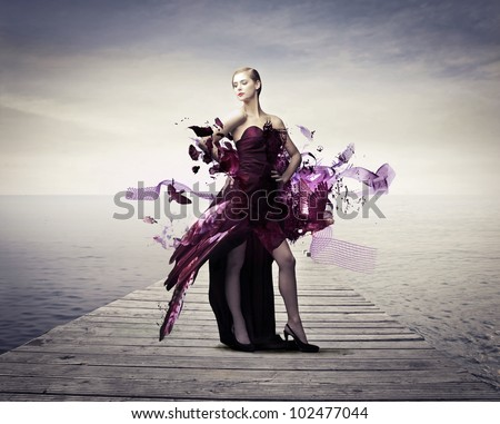 Beautiful elegant woman on a wharf with her dress melting away