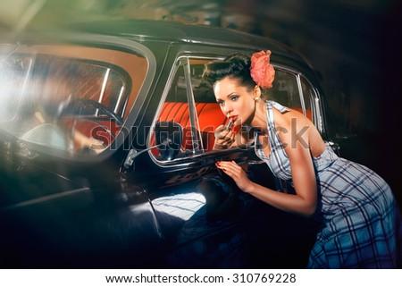 Beautiful elegant woman put lipstick on her lips near car mirror - stock photo