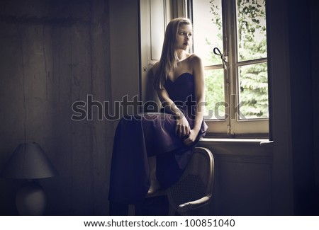 Beautiful elegant woman sitting in front of a window - stock photo