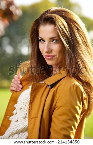 Beautiful elegant woman standing in a park in autumn