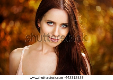 Beautiful elegant woman standing in a park in autumn. Portrait of happy young girl.