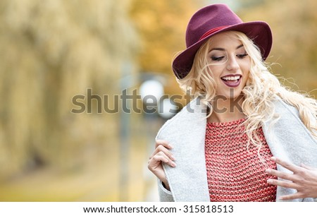 Beautiful elegant woman standing in  autumn park