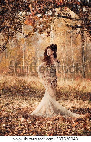 Beautiful elegant woman standing in the autumn forest in chiffon dress with yellow autumn leaves - stock photo