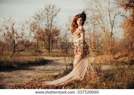 Beautiful elegant woman standing in the autumn park in chiffon dress with yellow autumn leaves - stock photo