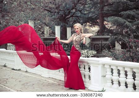 Beautiful elegant woman wearing in long mermaid fluttering fashion dress in winter park, outdoors full length portrait.  - stock photo