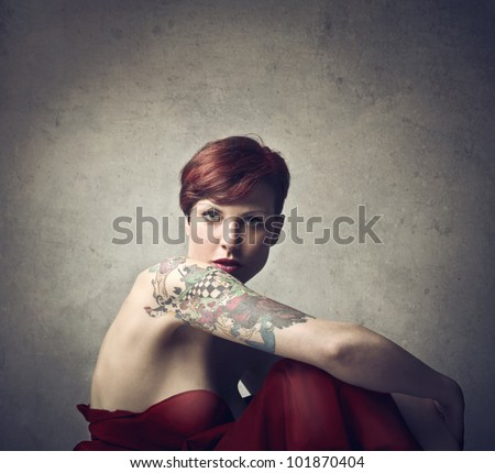 Beautiful elegant woman with a tattoo on her arm - stock photo