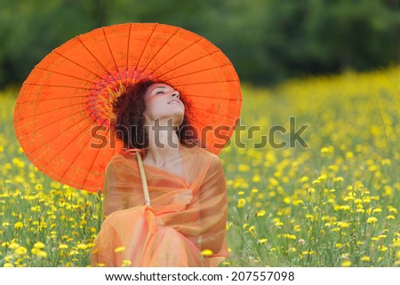 Beautiful elegant woman with an orange asian umbrella draped in a matching chiffon scarf sitting in dandelion summer field