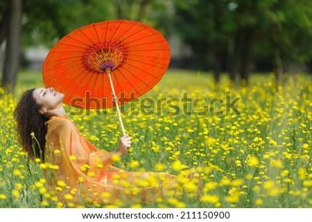 Beautiful elegant woman with an orange asian umbrella draped in a matching chiffon scarf sitting in dandelion summer field - stock photo