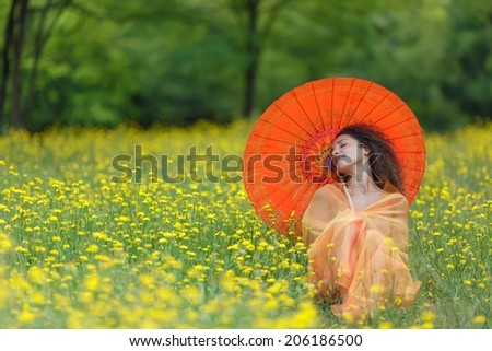 Beautiful elegant woman with an orange parasol draped in a matching chiffon scarf tilting back her head with a smile of bliss as she walks through a meadow filled with colorful yellow summer flowers