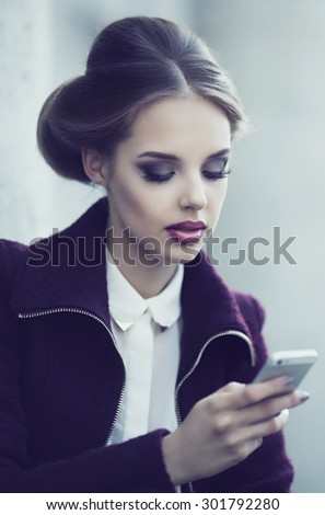 beautiful elegant woman with cellphone outdoor in the street - stock photo