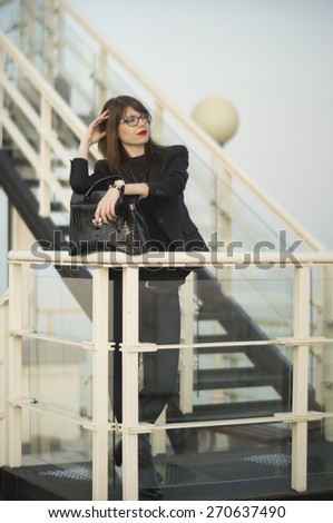 Beautiful elegant young business woman enjoying the view from the steps on the top of a building. - stock photo