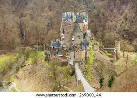 Beautiful Eltz Castle, a medieval castle located on a hill in the forest in Germany. On cold spring or autumn day from above. - stock photo