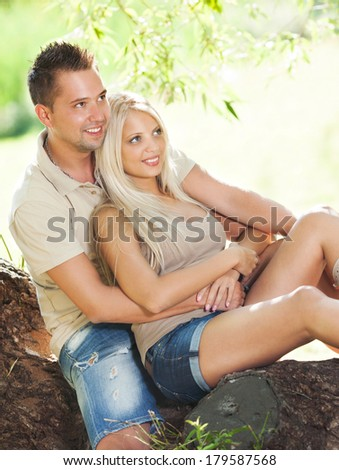 Beautiful embraced romantic couple in the park sitting on the tree