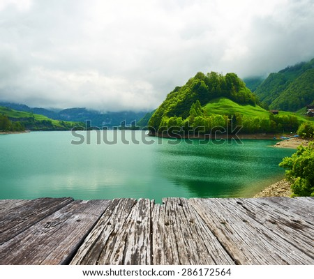 Beautiful emerald mountain lake in Switzerland under low clouds - stock photo