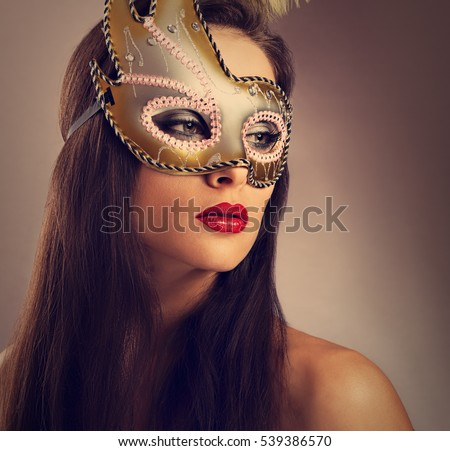 Beautiful emotion woman posing in carnival mask with bright makeup and red lipstick on empty copy space background. Closeup toned bright portrait