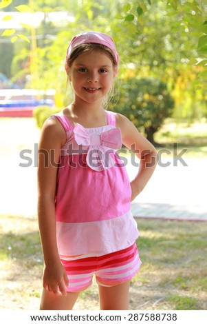 Beautiful emotional little girl in a summer dress and a pink bandana on a hot summer day - stock photo