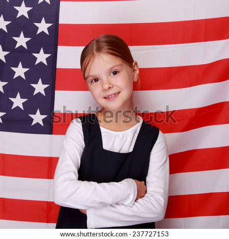 Beautiful emotional little girl on the background of the American flag