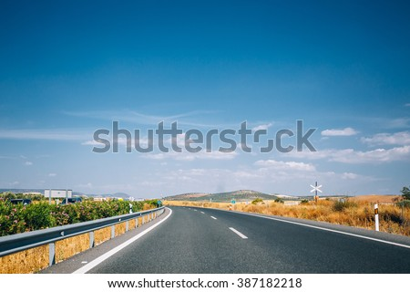 Beautiful empty asphalt freeway, motorway, highway against the background of southern Spanish landscape. Travel road concept. Andalusia, Spain. - stock photo