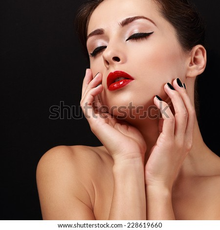 Beautiful enjoying makeup woman with red lips touching her health skin the beauty skin hand with closed eyes on black background - stock photo