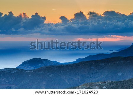 Beautiful ethereal mountain sunset at twilight with atmospheric blue lighting on the peaks and a towering formation of cumulus cloud in the orange sky - stock photo