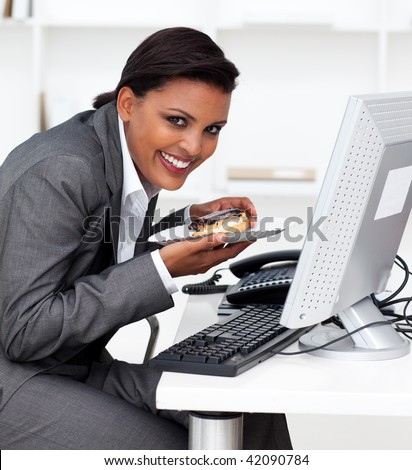 Beautiful ethnic businesswoman eating a pastry at work