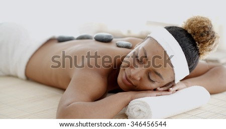 Beautiful ethnic client being treated with hot stone therapy at a luxury health spa  - stock photo