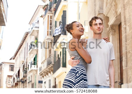 Beautiful ethnically diverse couple playfully hugging in picturesque destination city street, joyfully smiling, sightseeing. Boyfriend and girlfriend together on holiday, travel recreation lifestyle.