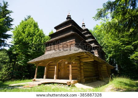 Beautiful ethno rustic church with wooden roof in the forest. Summer landscape with a lonely mountain village in the Ukrainian Carpathians. - stock photo