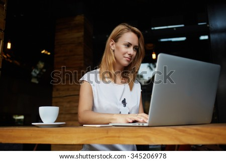 Beautiful European female student sitting with portable laptop computer in modern coffee shop interior, successful female freelancer using net-book for distance work during morning breakfast in cafe  - stock photo