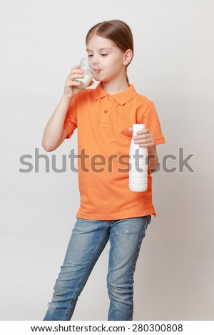 Beautiful european little girl holding cow milk in glass - stock photo