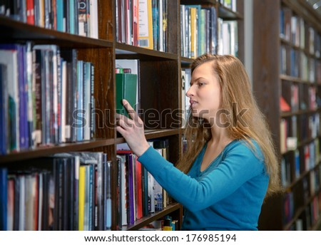 Beautiful european student girl standing by a bookshelf in a library and choosing a book
