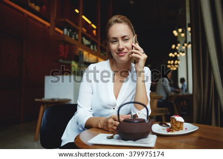 Beautiful European woman calling with her mobile phone while relaxing in cafe during coffee break, young hipster girl phoning via cell telephone while resting after strolling outdoors during free time - stock photo