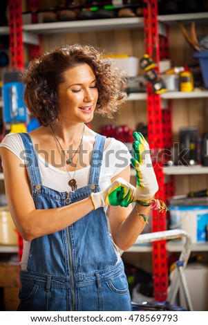 beautiful european woman mechanic wearing protective gloves
