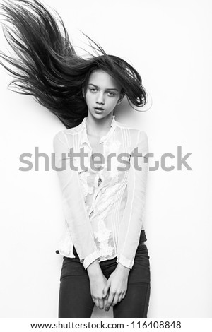 Beautiful European young fashion model woman standing with hands folded against white background - stock photo